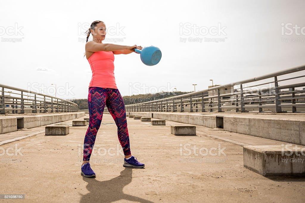 Sportswoman exercising with kettlebell on the bridge stock photo