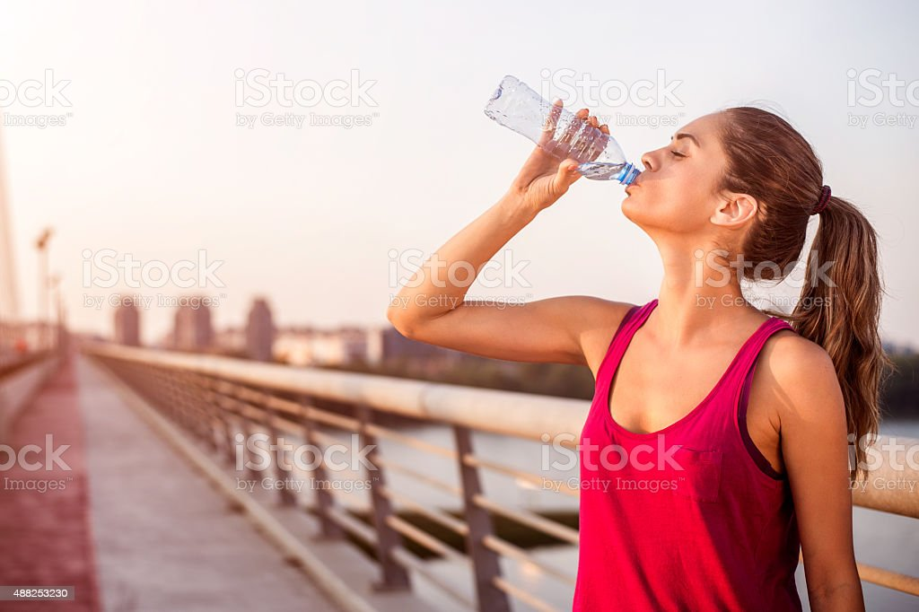 Young sportswoman with pony tail drinking water on the bridge while...