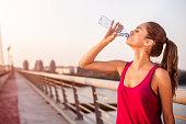 Sportswoman hydrating on the bridge