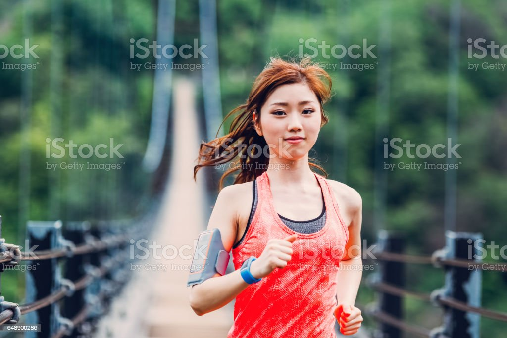 Sportswoman jogging at the bridge stock photo