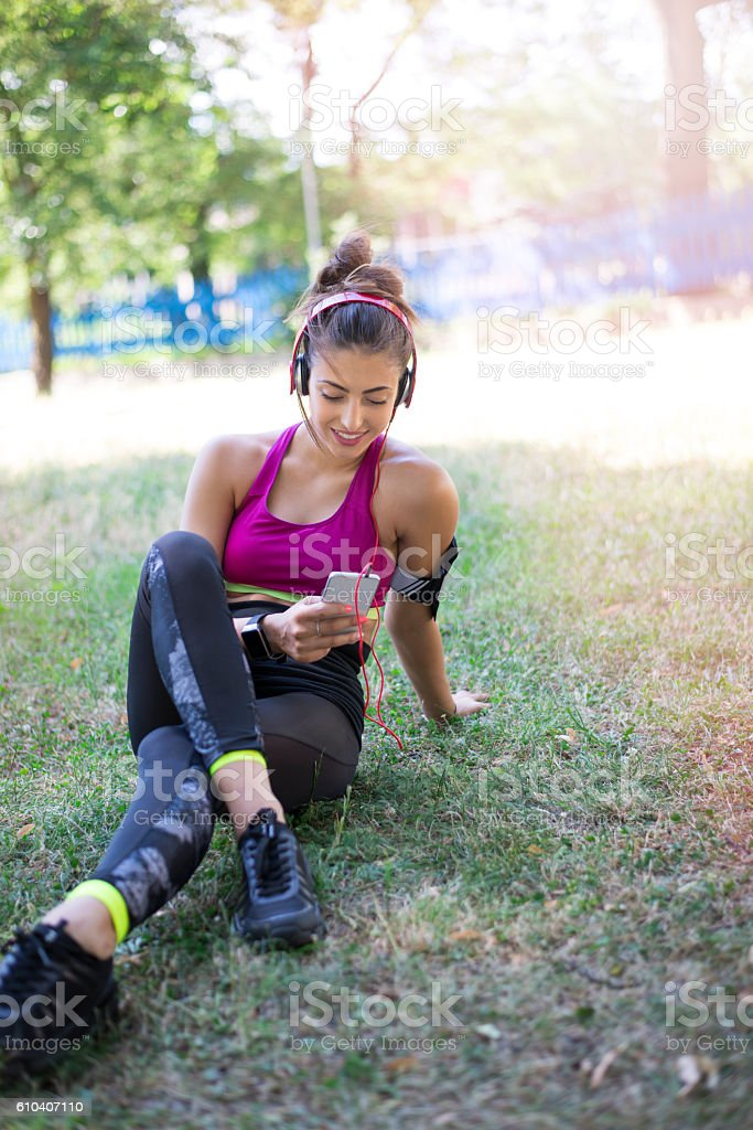 Sportswoman listening to music using smartphone stock photo