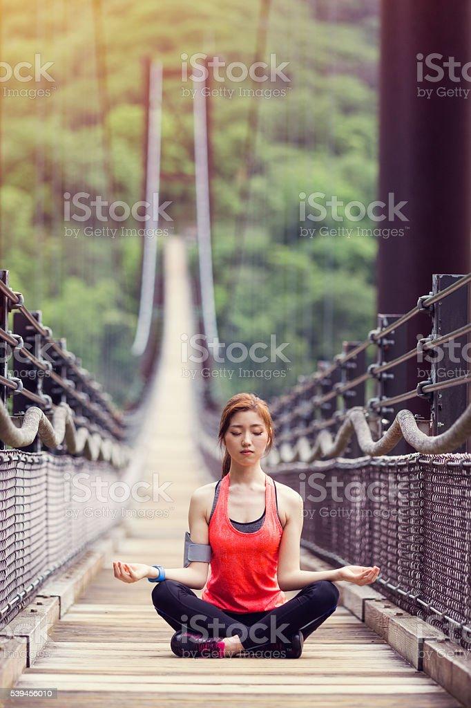 Sportswoman practicing yoga at the rope bridge stock photo