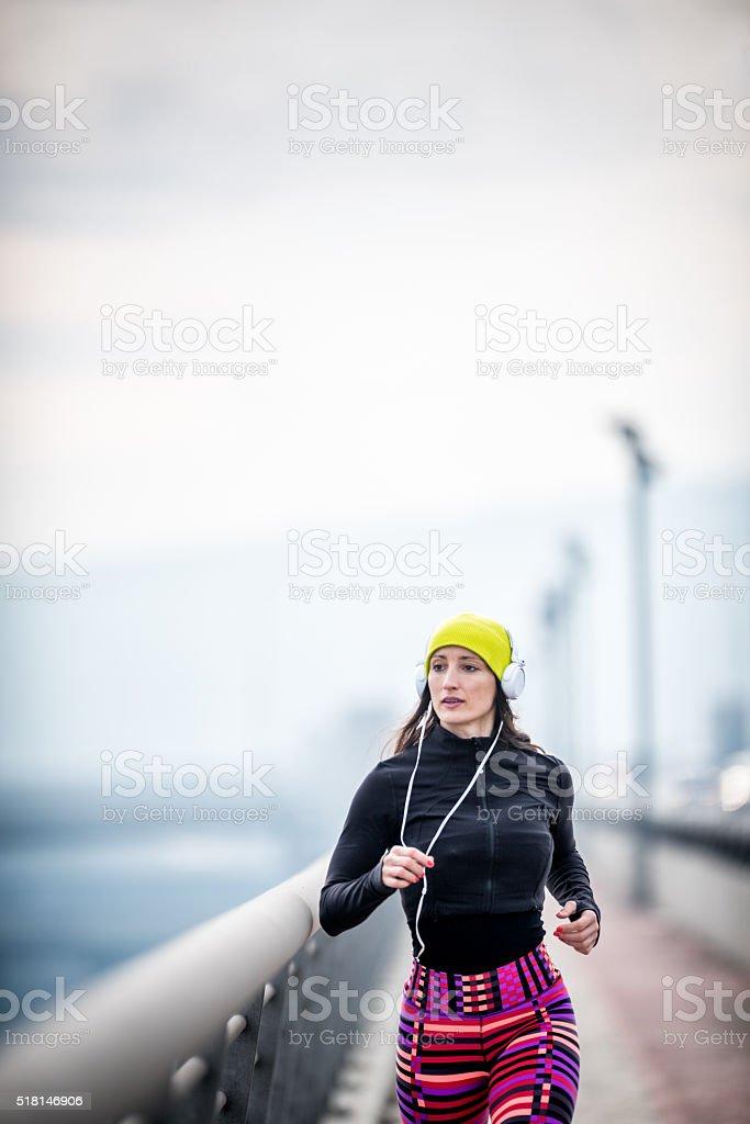Sportswoman running in the winter morning stock photo