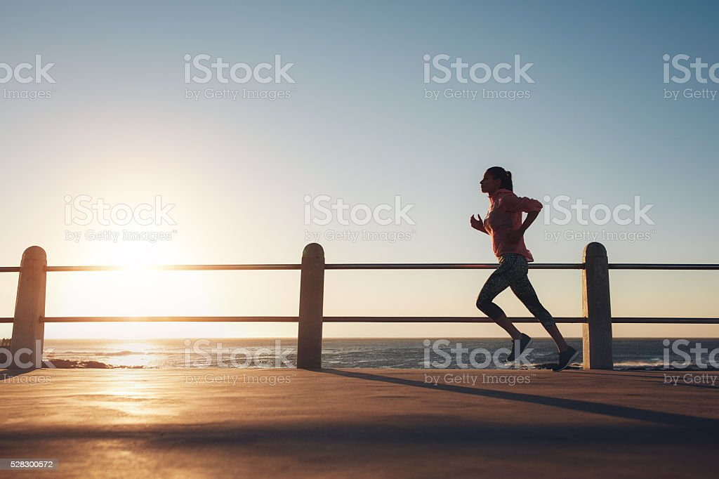 Sportswoman running on a road by the sea stock photo
