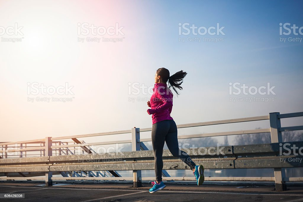 Sportswoman running over the bridge in the morning royalty-free stock photo