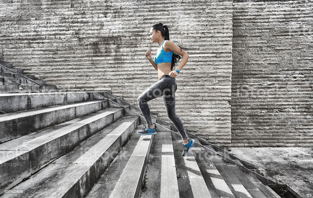 Sportswoman running up on stone stairs-side view stock photo