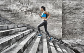 Sportswoman running up on stone stairs-side view