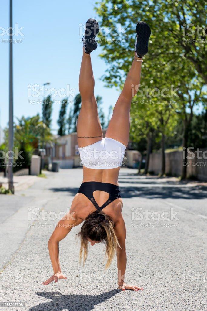 Sportswoman training handstand & hand walk stock photo