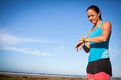 Sportswomen checking her smart watch up watch before her run