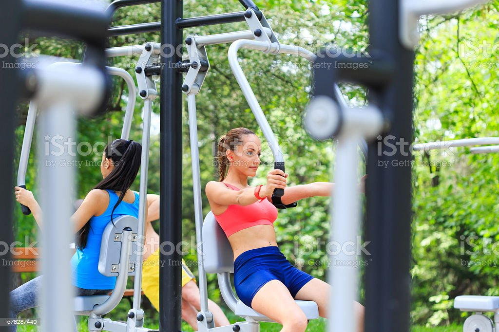 Sportswomen practicing on chest press in the park stock photo
