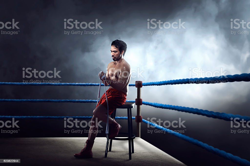 Sporty asian boxer man sitting on ring while wearing strap stock photo