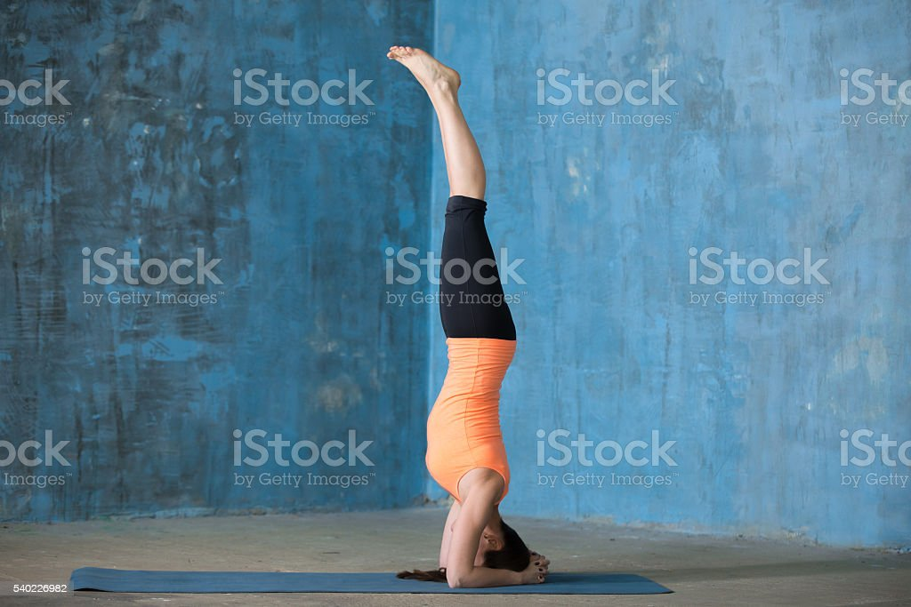 Sporty beautiful young woman doing headstand stock photo