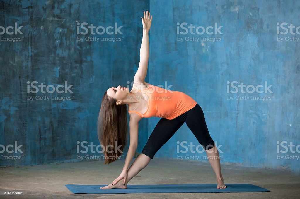 Sporty beautiful young woman doing Trikonasana stock photo