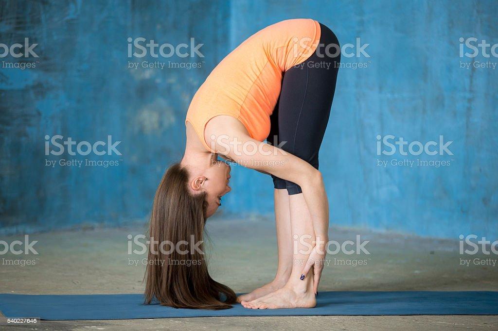 Sporty beautiful young woman Doing Uttanasana pose stock photo