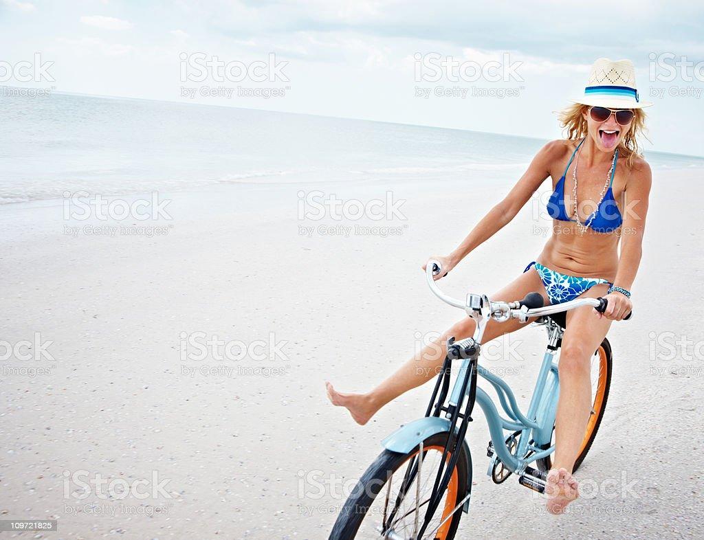 Sporty bikini female riding bicycle on beach royalty-free stock photo