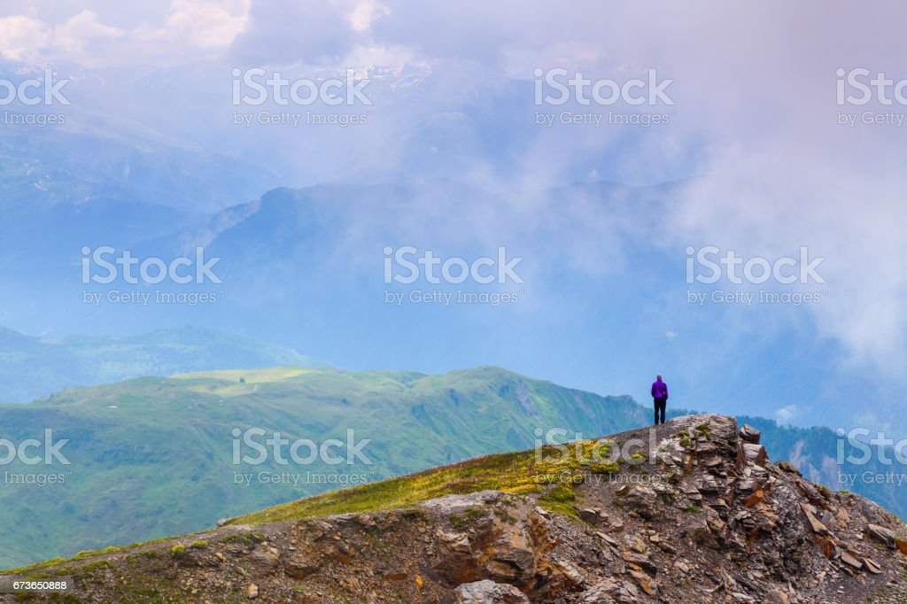 Sporty boy standing at the edge of the precipice and watching on the endless vast of mountains landscape in the sunny day. Upper Svaneti, Georgia, Europe. stock photo