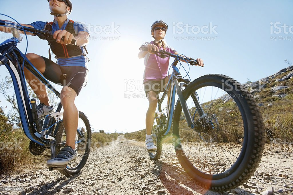 Sporty couple bike riding in a remote area royalty-free stock photo
