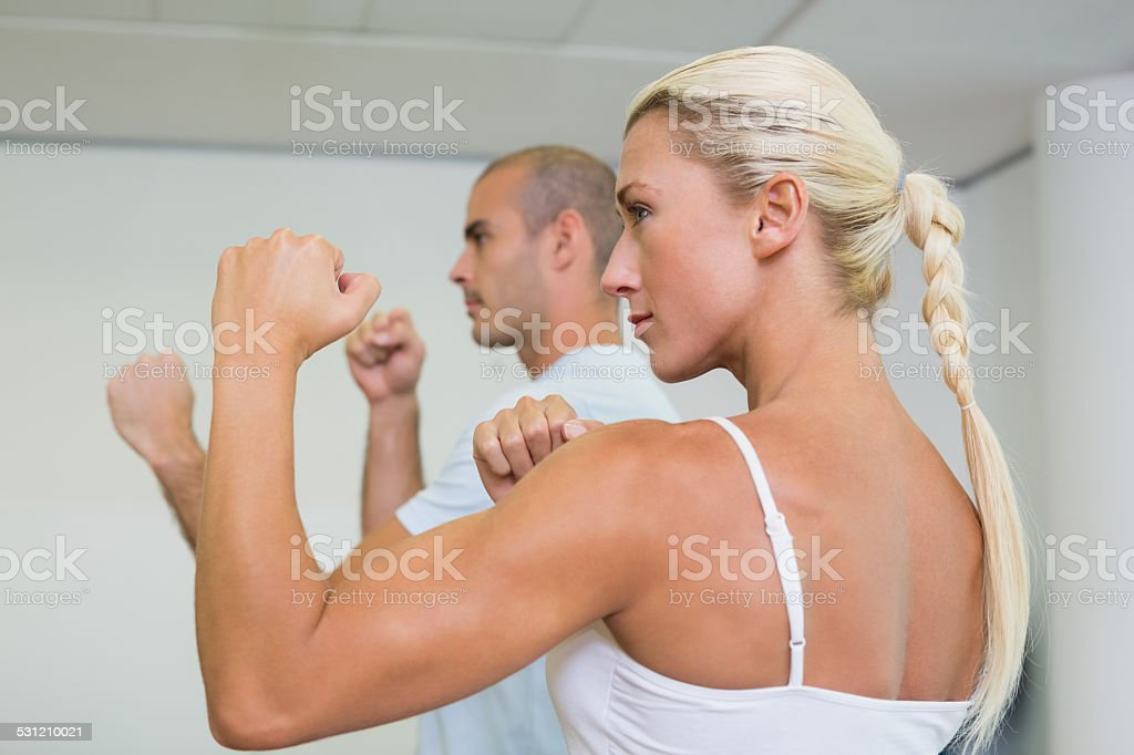 Sporty couple clenching fists at fitness studio stock photo