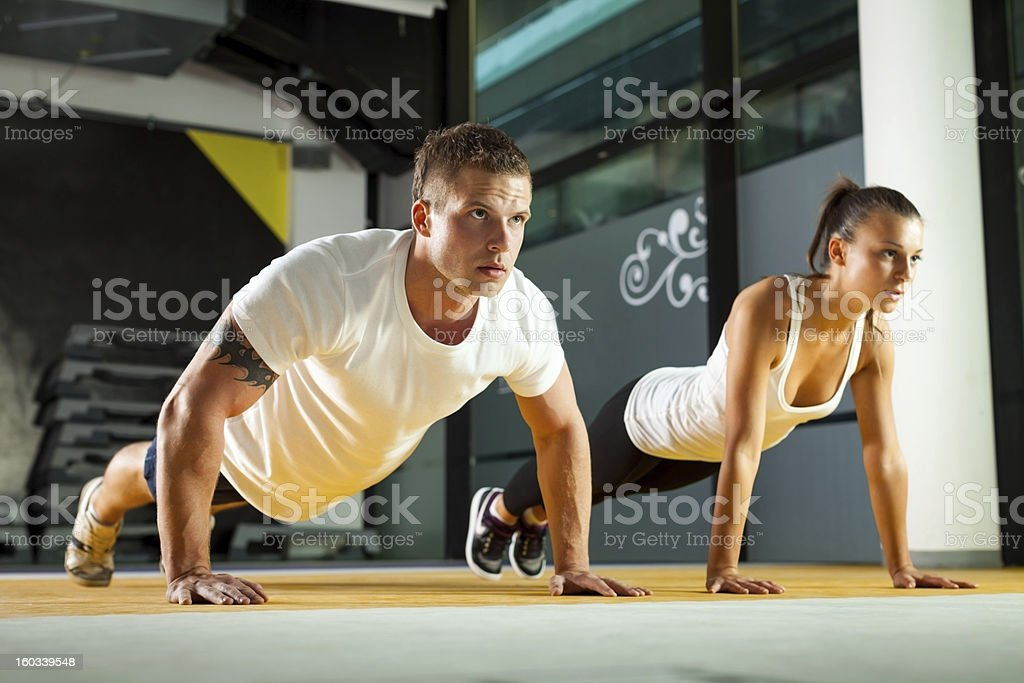Sporty couple exercising at the fitness gym royalty-free stock photo