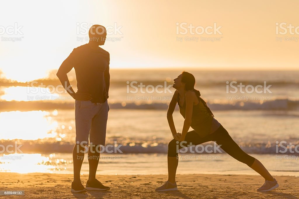Sporty couple on shore at beach during sunset stock photo