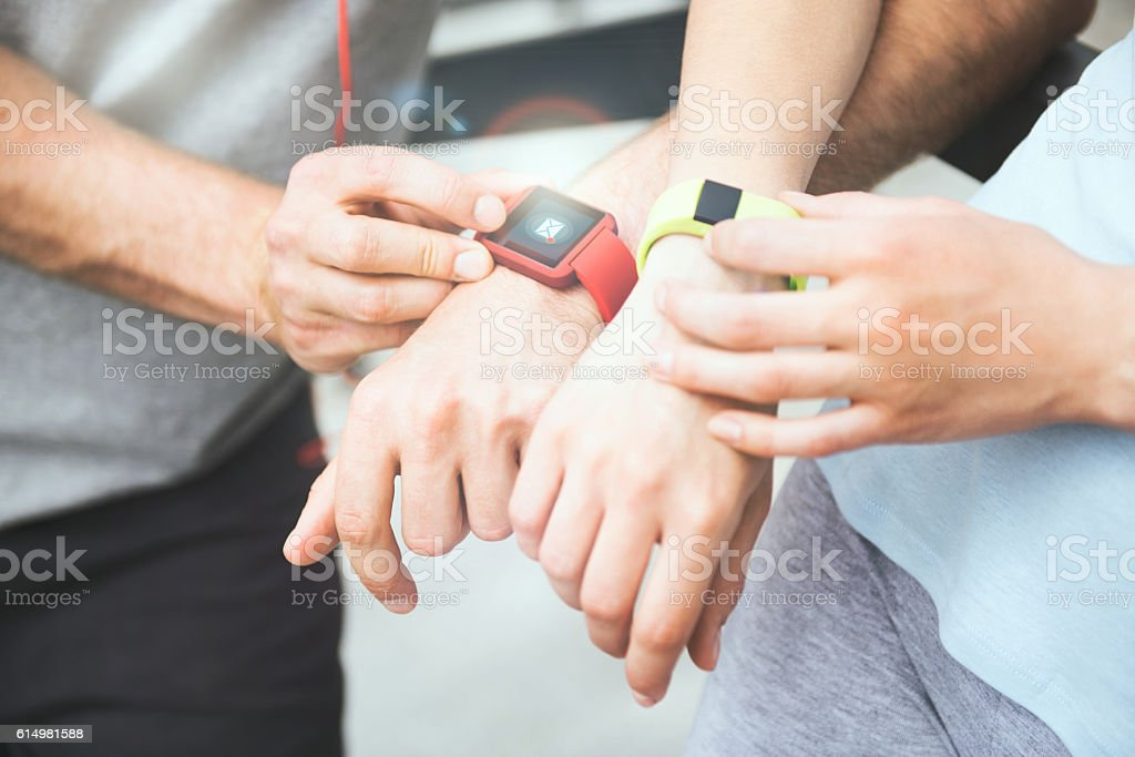 Sporty couple sharing workout data from their smartwatches. stock photo