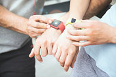 Sporty couple sharing workout data from their smartwatches.