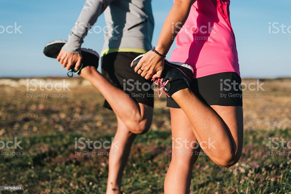 Sporty couple stretching legs outdoors before trail running workout outdoors stock photo