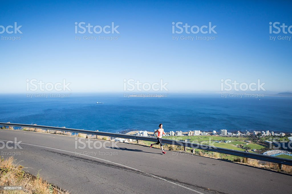 Sporty female running early above the city stock photo