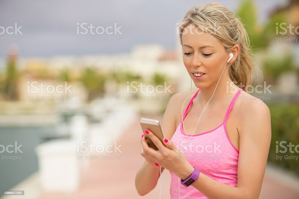 Sporty fit girl using smartphone outdoors stock photo