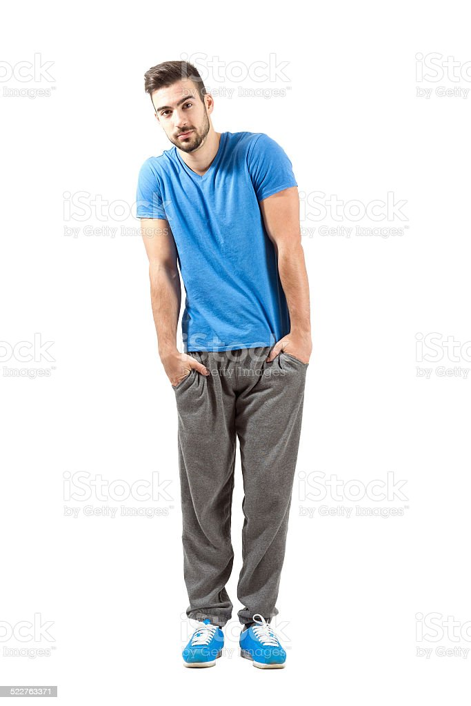 Sporty fit guy with hands in pocket looking at camera stock photo