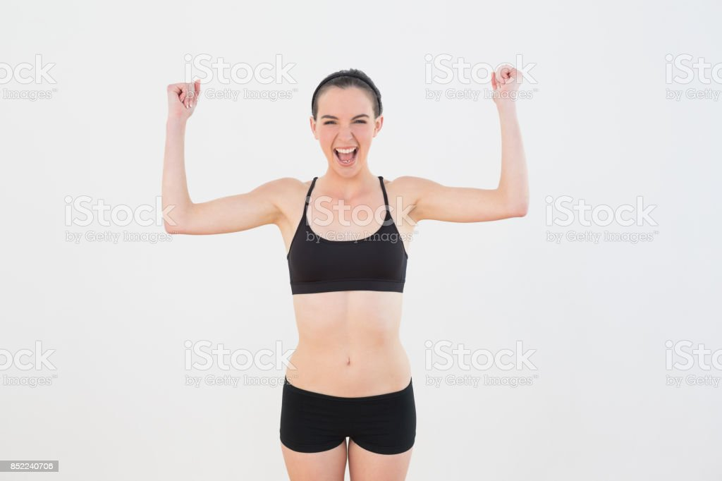 Sporty fit woman clenching fists against wall stock photo
