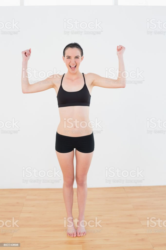 Sporty fit woman clenching fists in fitness studio stock photo