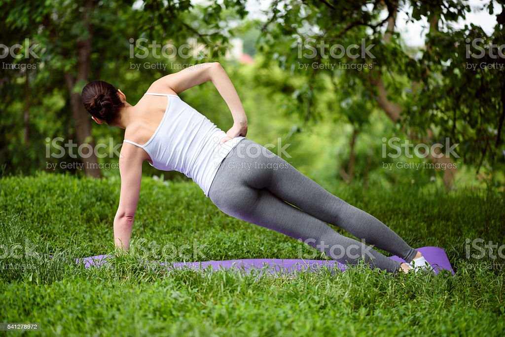 Sporty fit woman exercising in park stock photo