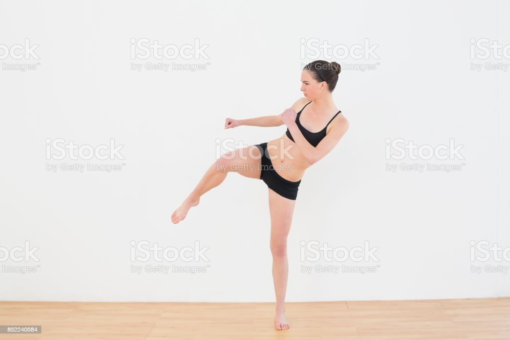 Sporty fit woman performing an air kick in fitness studio stock photo
