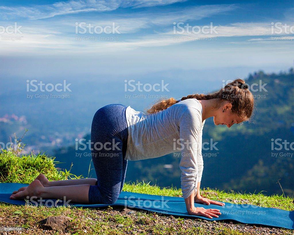 Sporty fit woman practices yoga asana bitilasana outdoors stock photo