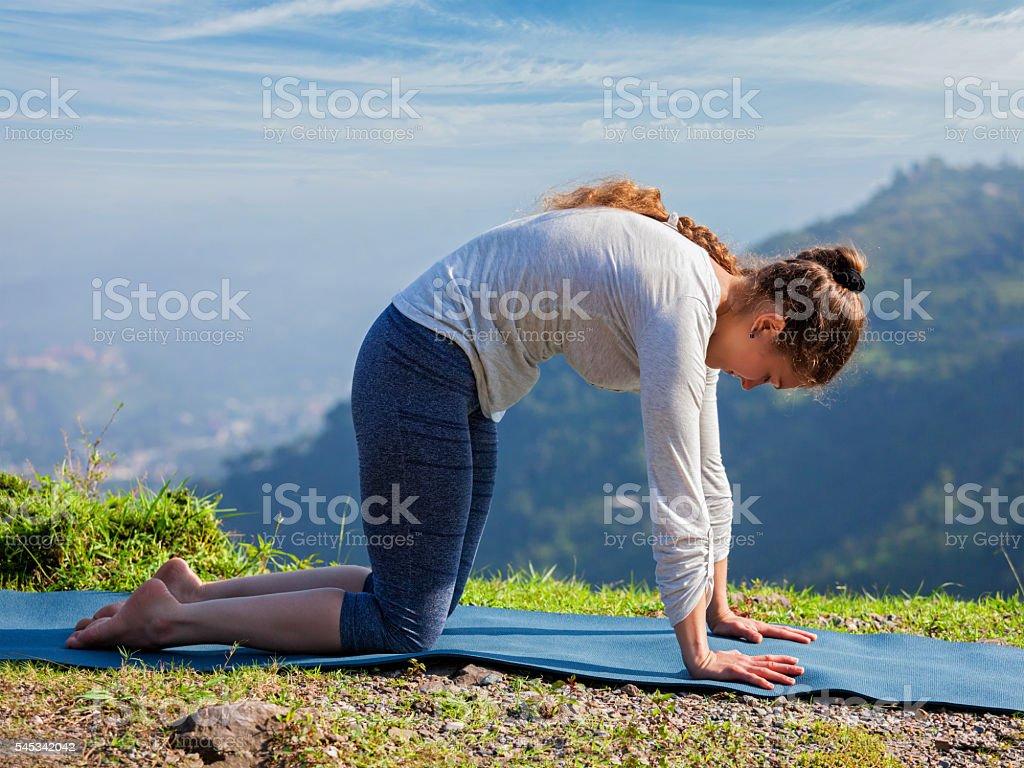 Sporty fit woman practices yoga asana Marjariasana outdoors stock photo