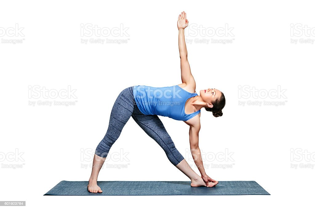 Sporty fit woman practices yoga asana utthita trikonasana stock photo