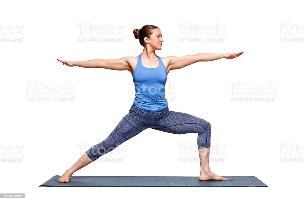 Sporty fit woman practices yoga asana utthita Virabhadras stock photo