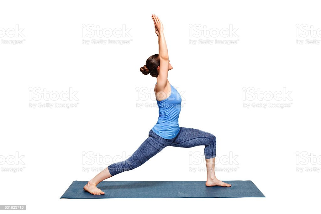 Sporty fit woman practices yoga asana utthita Virabhadras stock photo