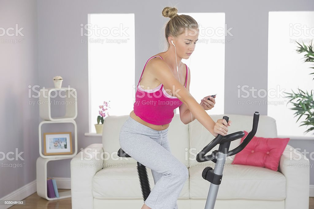 Sporty focused blonde training on exercise bike listening to mus stock photo