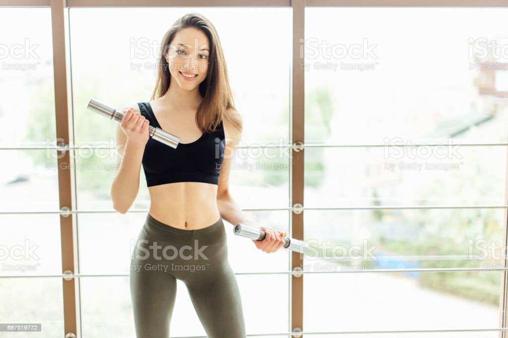 Sporty girl do exercise for biceps on white background stock photo