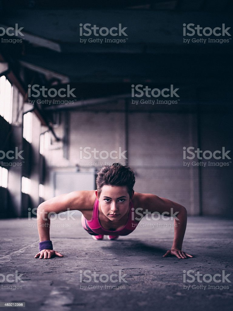 Sporty girl doing push ups and looking determined stock photo