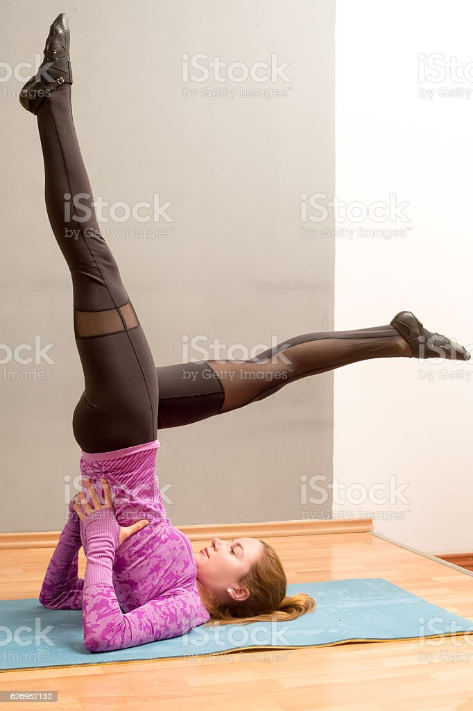 Sporty girl on white background doing shoulder stand exercise stock photo