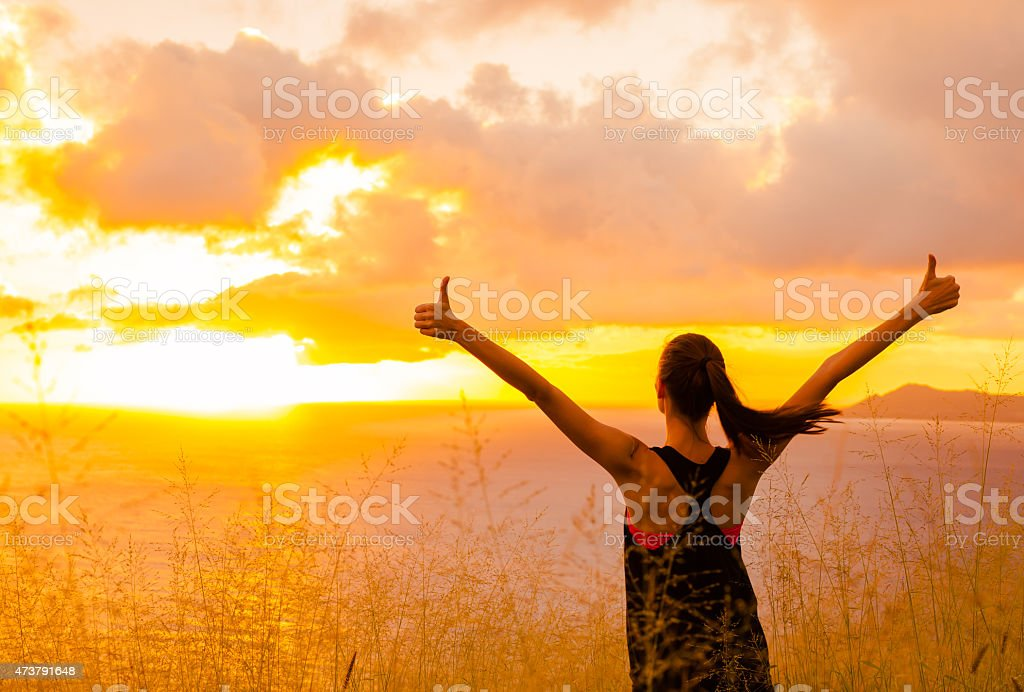 Sporty girl raising arms towards beautiful glowing sunshine. stock photo