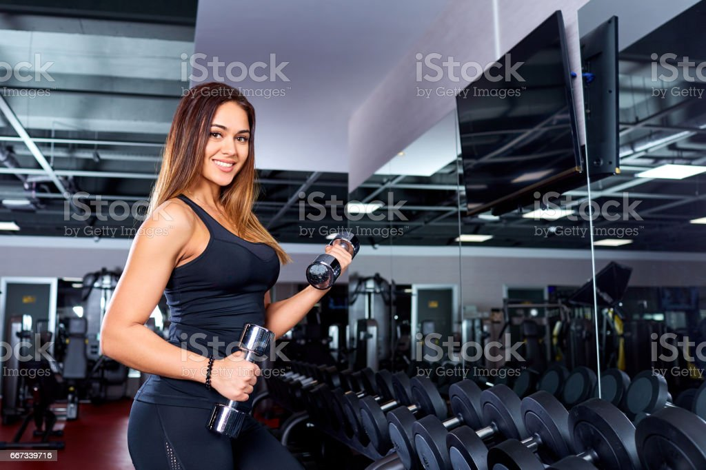 Sporty girl with dumbbells in the gym. stock photo