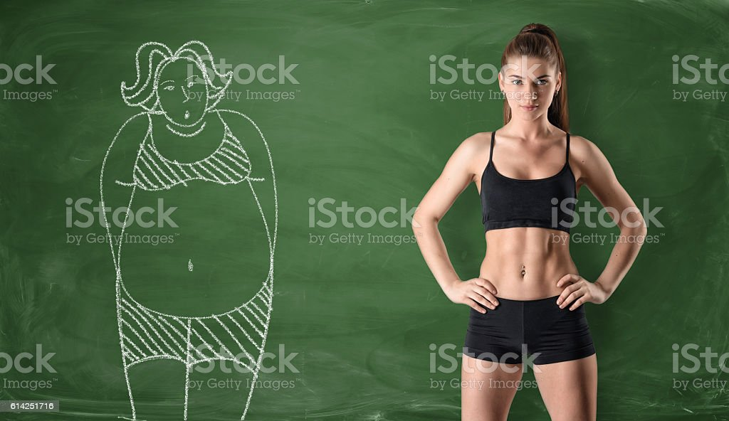 Sporty girl with slim body and picture of fat woman stock photo