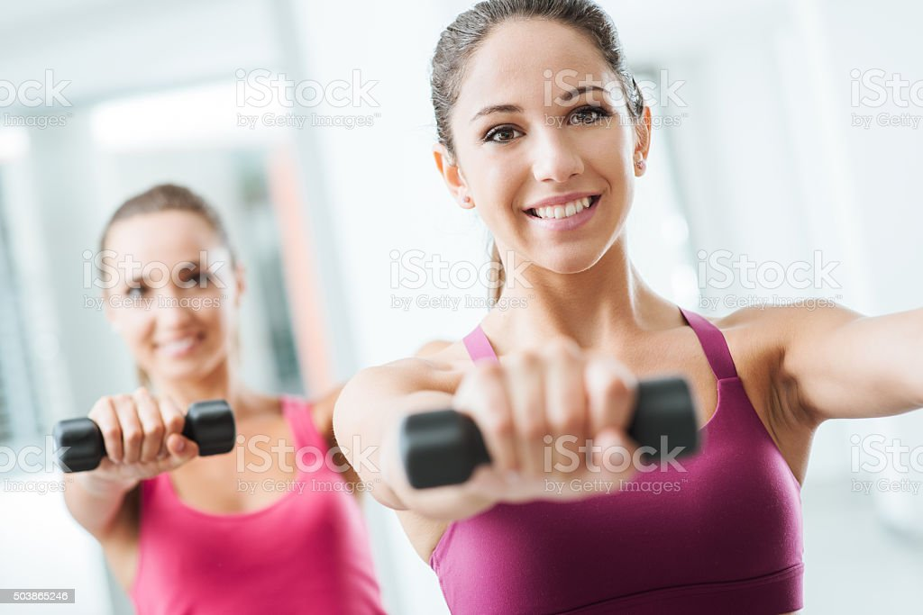 Sporty girls weightlifting at gym stock photo