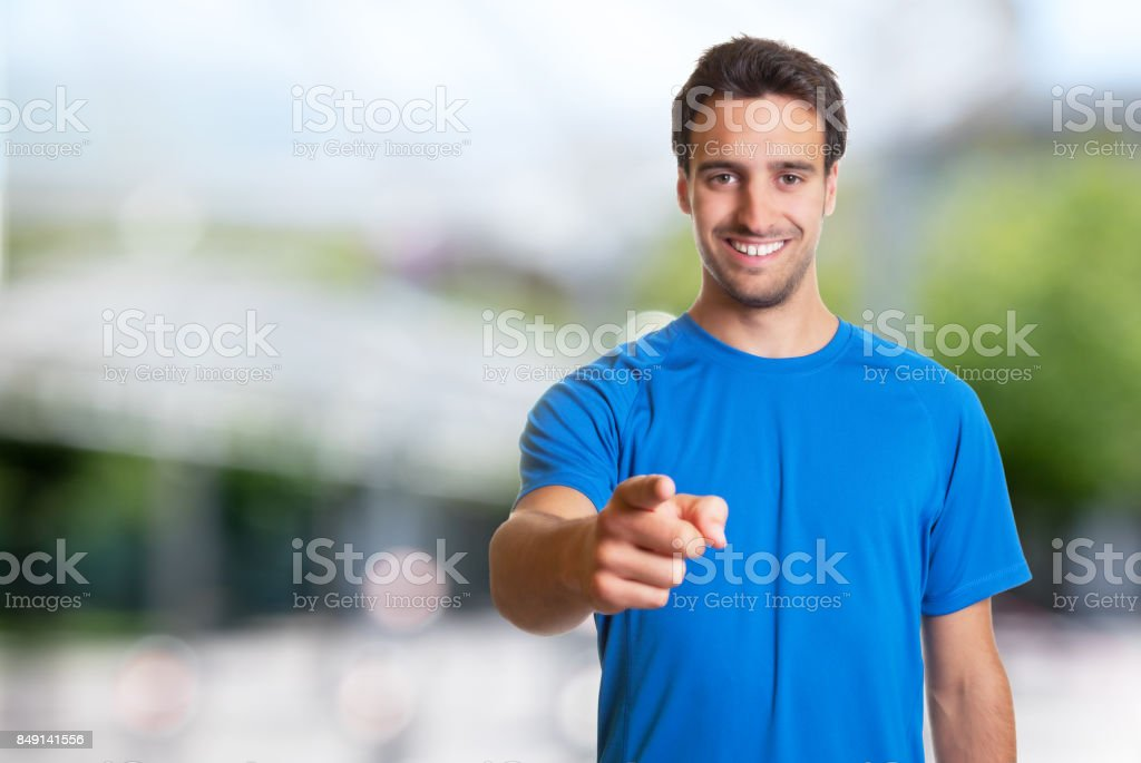 Sporty hispanic man with beard pointing at camera stock photo