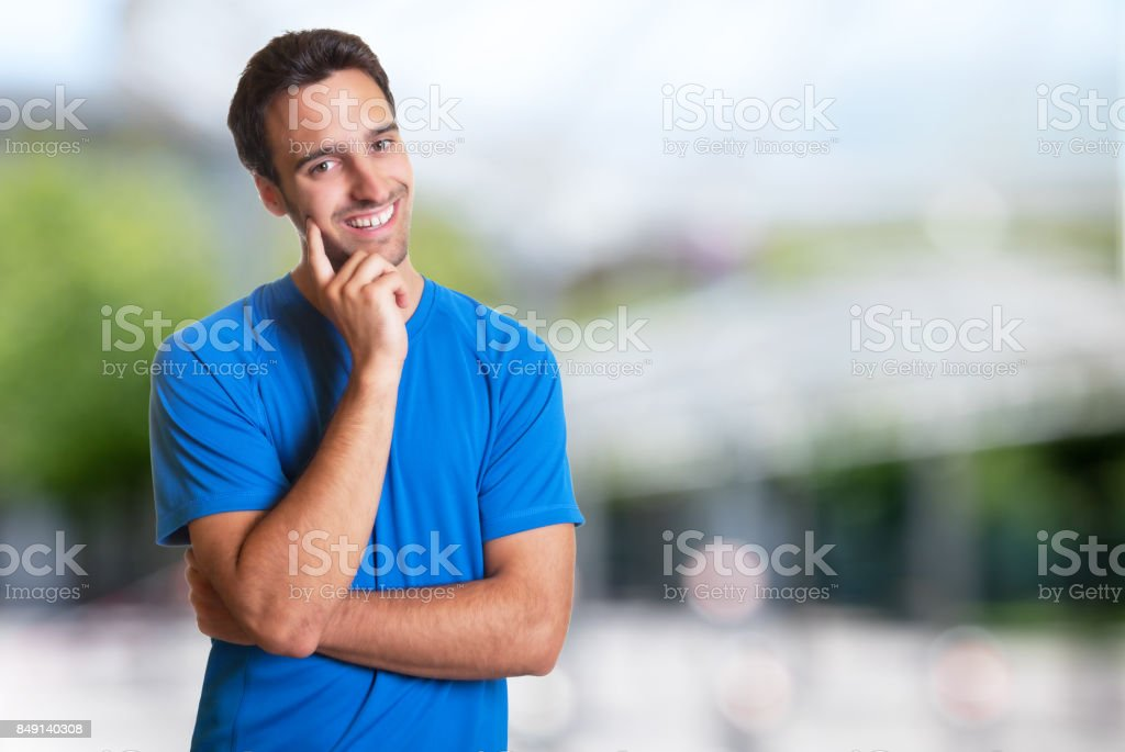 Sporty hispanic man with beard smiling at camera stock photo