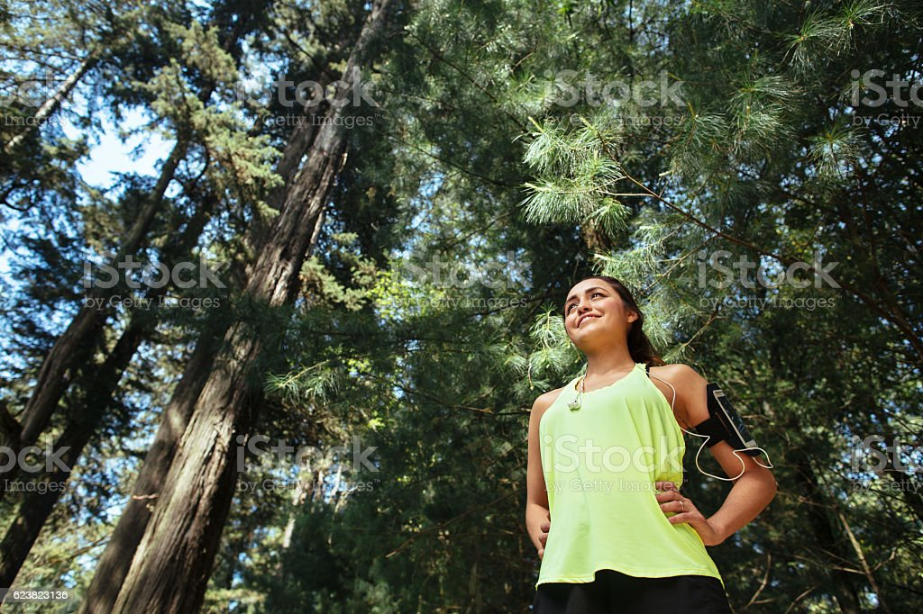 Sporty latin woman standing and smiling away outdoors stock photo